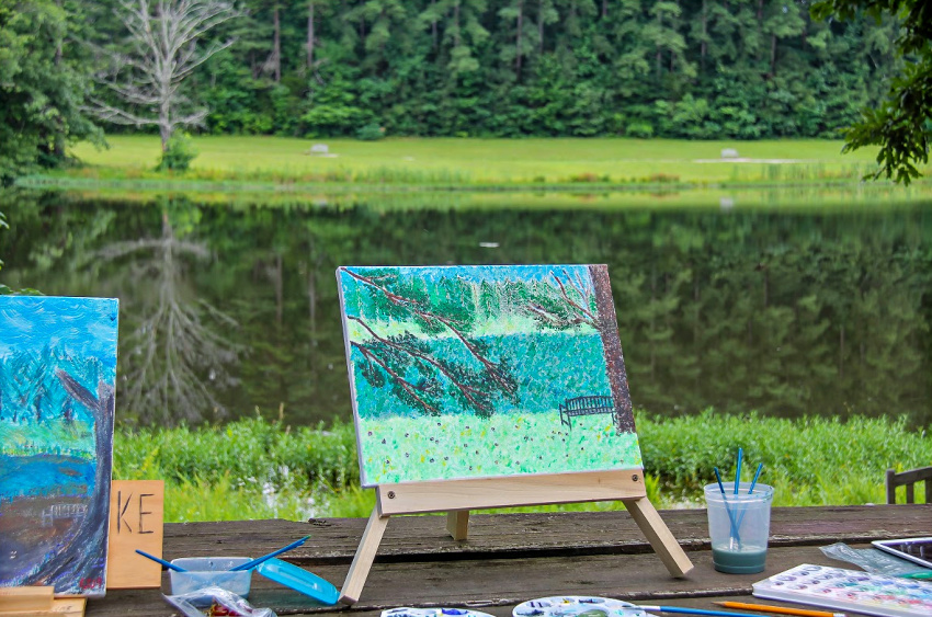 outdoor landscape painting on canvas is done by a lake.