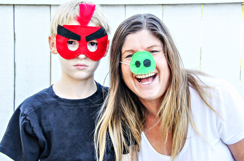 A mother and son wearing handmade angry birds face masks.