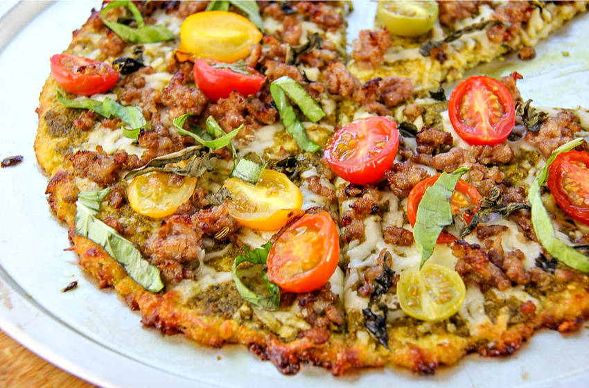 Cauliflower pizza crust topped with tomatoes, pesto, and sausage.