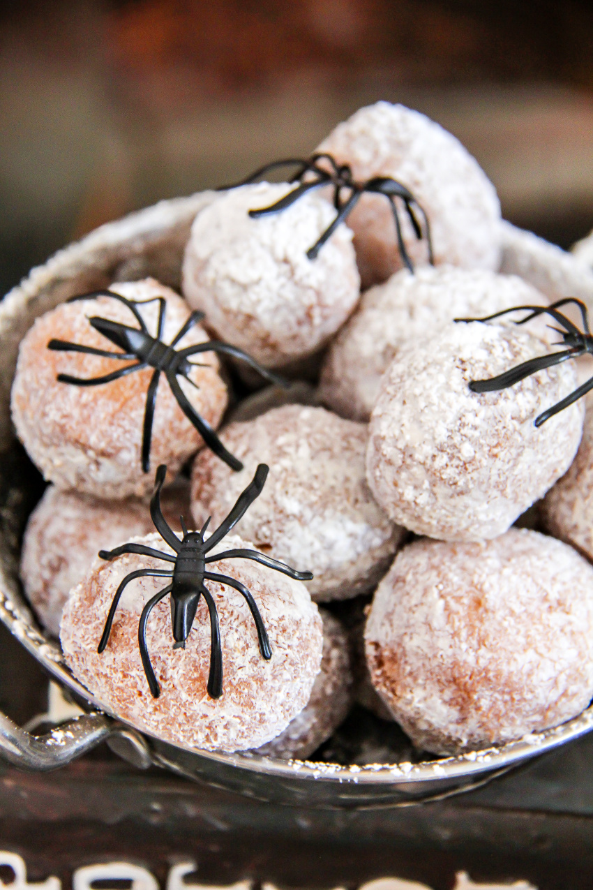White powdered donut holes with plastic spiders on them.