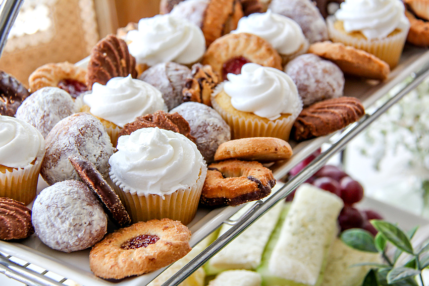 Assorted cookies, mini cupcakes, and donut holes on a tray for an afternoon tea party.