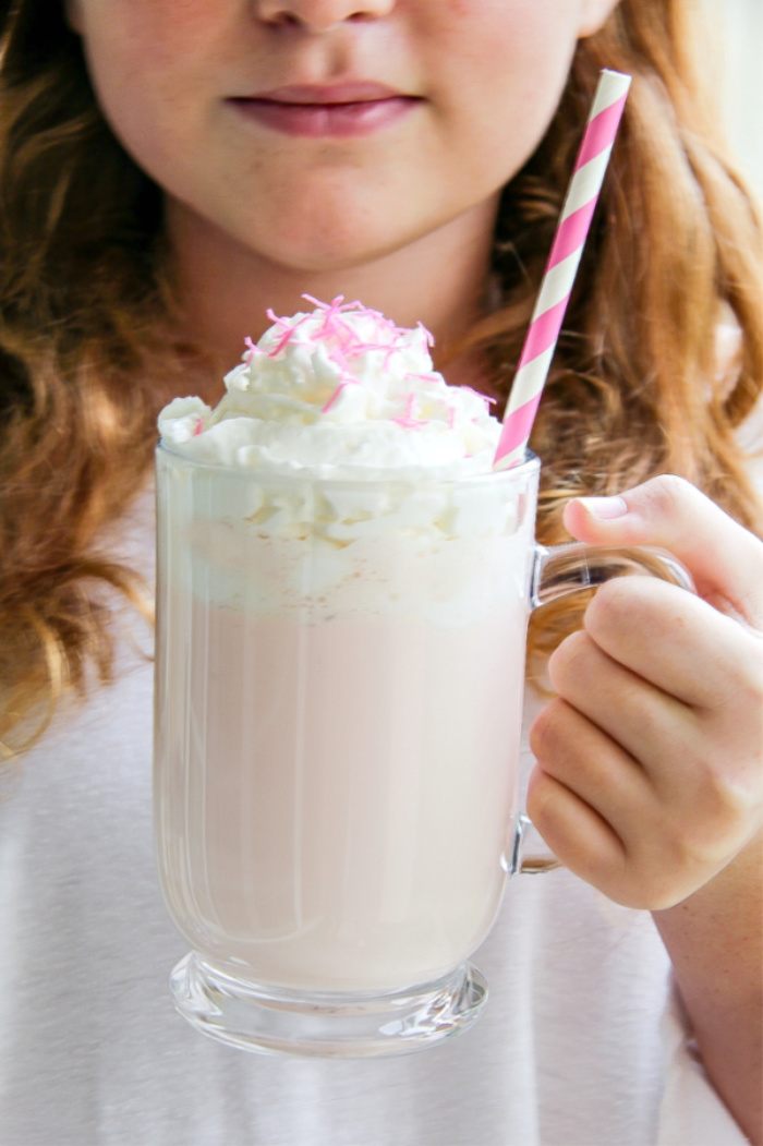 girl holding a pink hot chocolate in a clear mug
