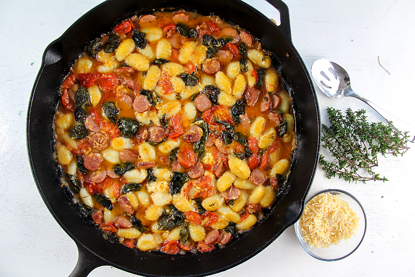 a cast-iron pan with gnocchi and kielbasa and cooked produce