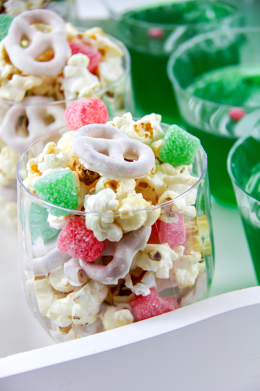 popcorn, yogurt covered pretzels, and red and green candy in a cup