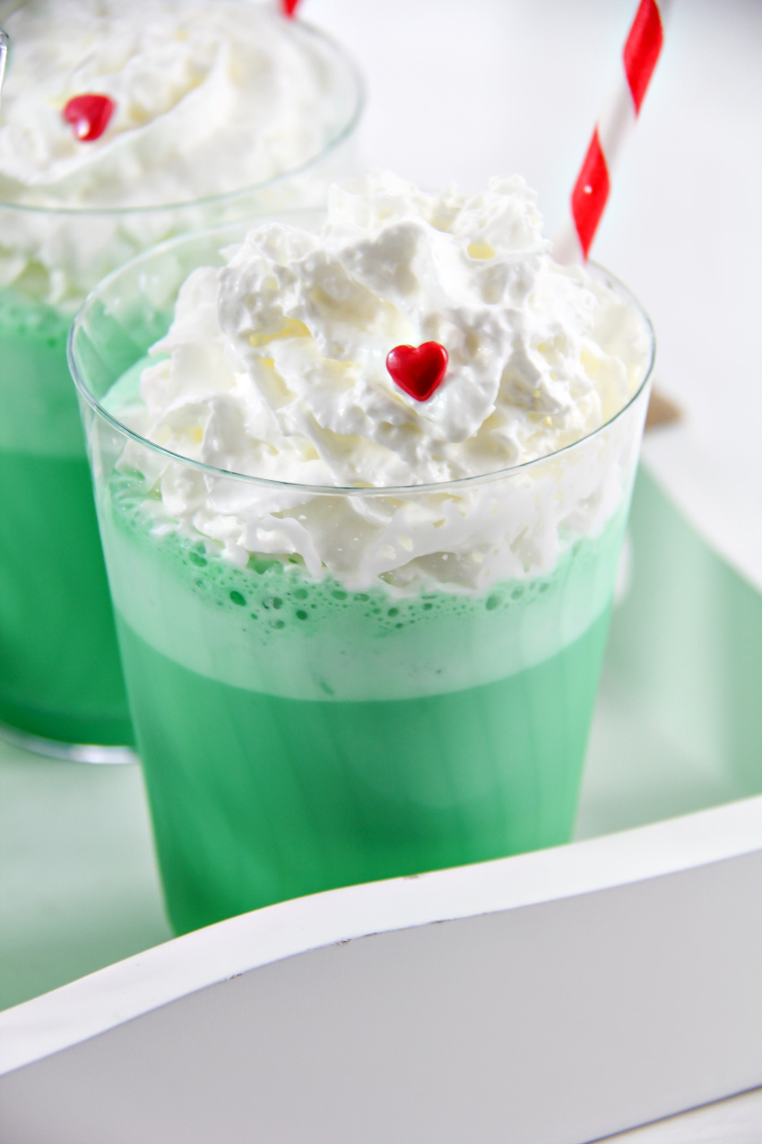 a green milkshake with whipped cream and a red candy heart