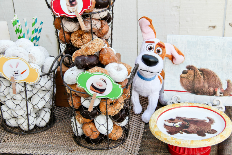 Baskets of donuts, candy, and Secret Life of Pets tableware for a movie night with kids.