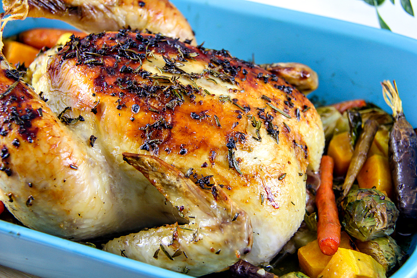 a whole roast chicken with vegetables in a blue baking dish