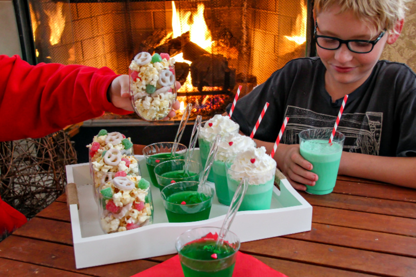 kids enjoying red, green, and white food in front of a fire