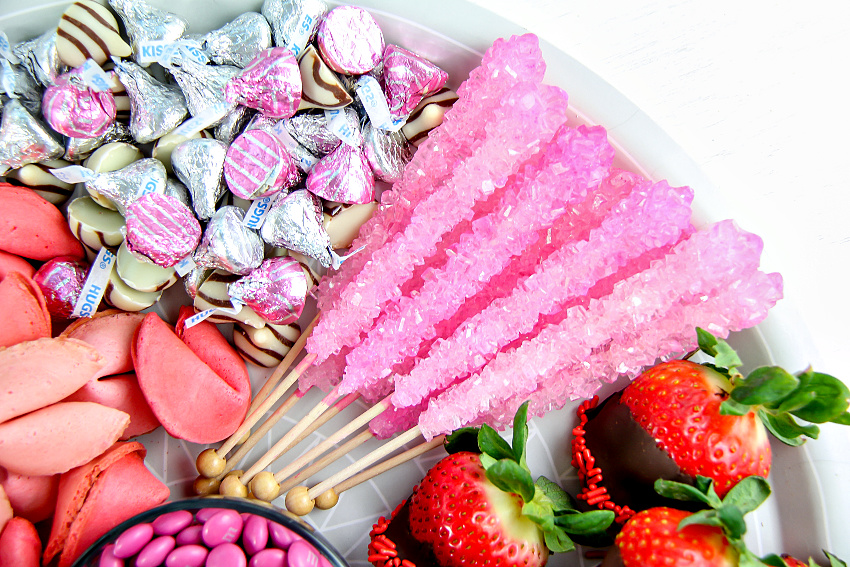 rock candy lollipops and hershey's kisses with chocolate covered strawberries and pink fortune cookies