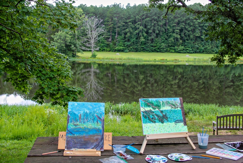 art easels and paints in front of a lake with green trees