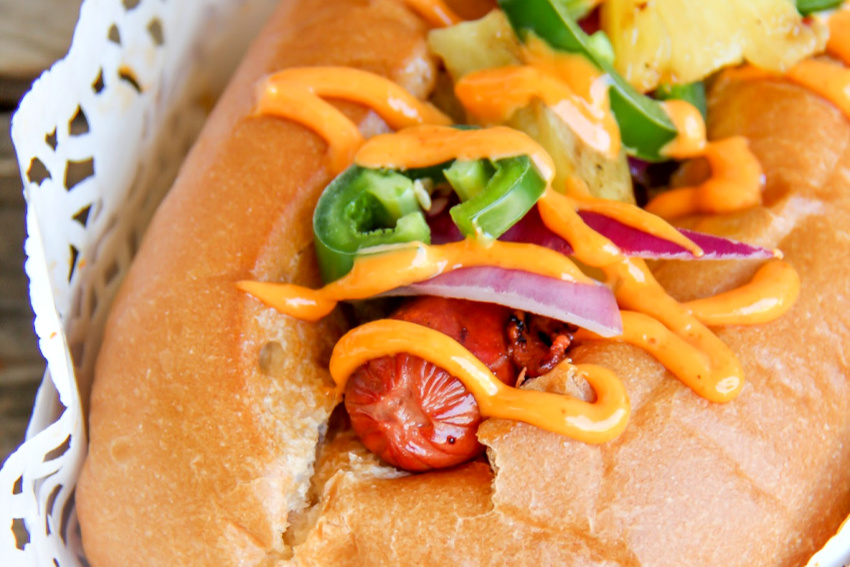 a hot dog in a bun topped with jalapeno, red onion, and sriracha sauce