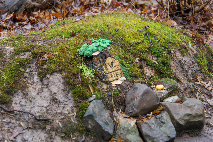 a fairy home with a heart door in a mossy covered mound with rocks