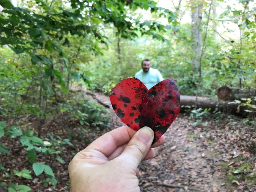 red leaves being held in a heart shape in front of a man