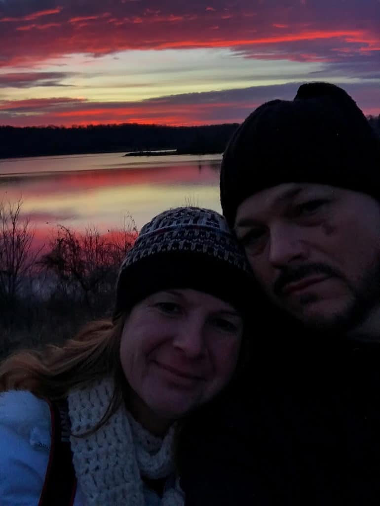 a couple standing in front of a pink and purple sunrise over a lake