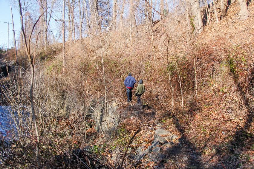 Man and boy walking along cliff edge through brush and barren trees