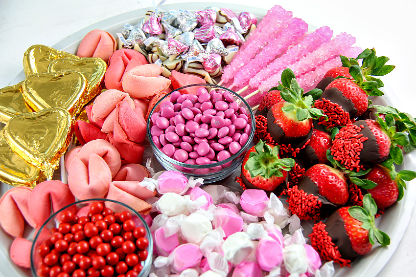 a candy tray for Valentine's Day filled with fortune cookies, chocolate covered strawberries and pink candies.