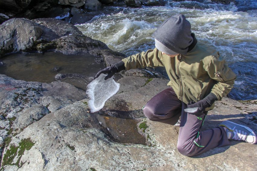 boy lifting ice off a rock pool with river in the background