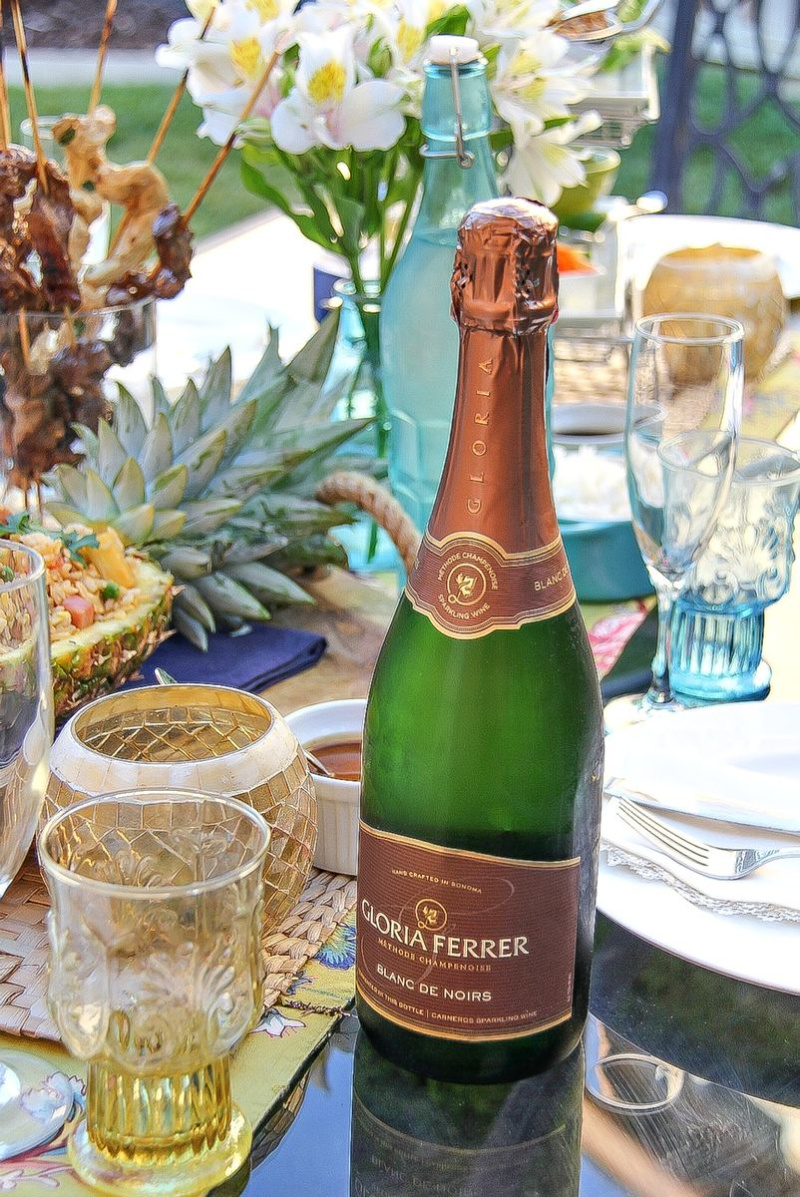 A bottle of Gloria Ferrer Sparkling on an outdoor table with Thai food.