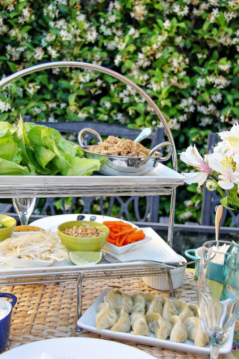 a tiered tray on a table filled with ingredients to make lettuce wraps
