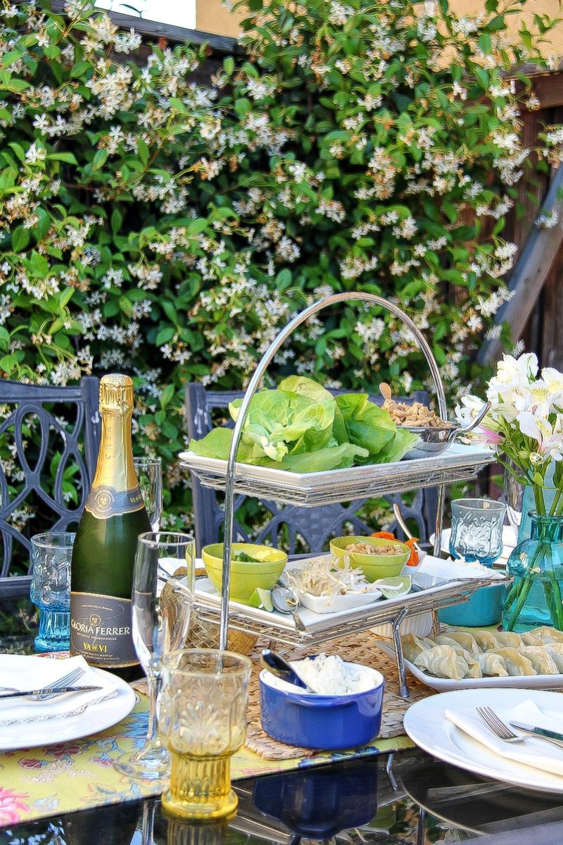 An outdoor dining table with a tiered tray containing ingredients to make lettuce wraps