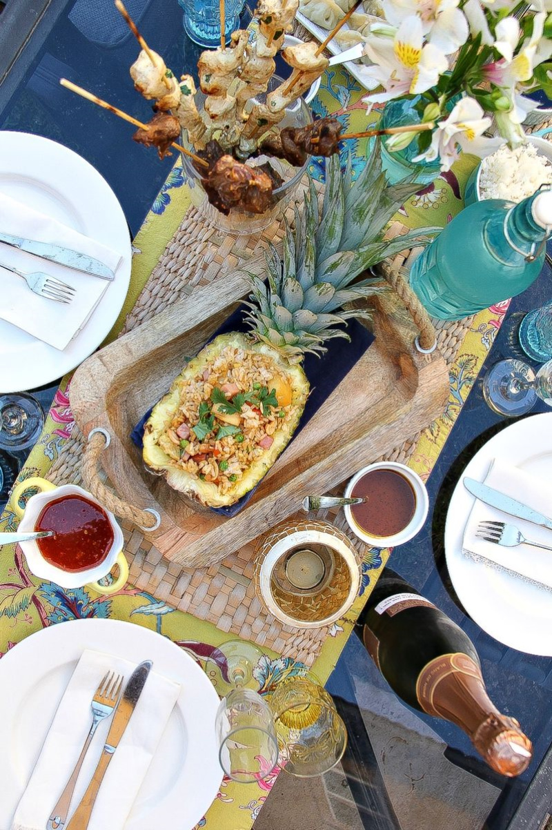 Looking down over an outdoor table with a half pineapple filled with pineapple fried rice, kabobs in a glass dish, flowers, and dining ware.