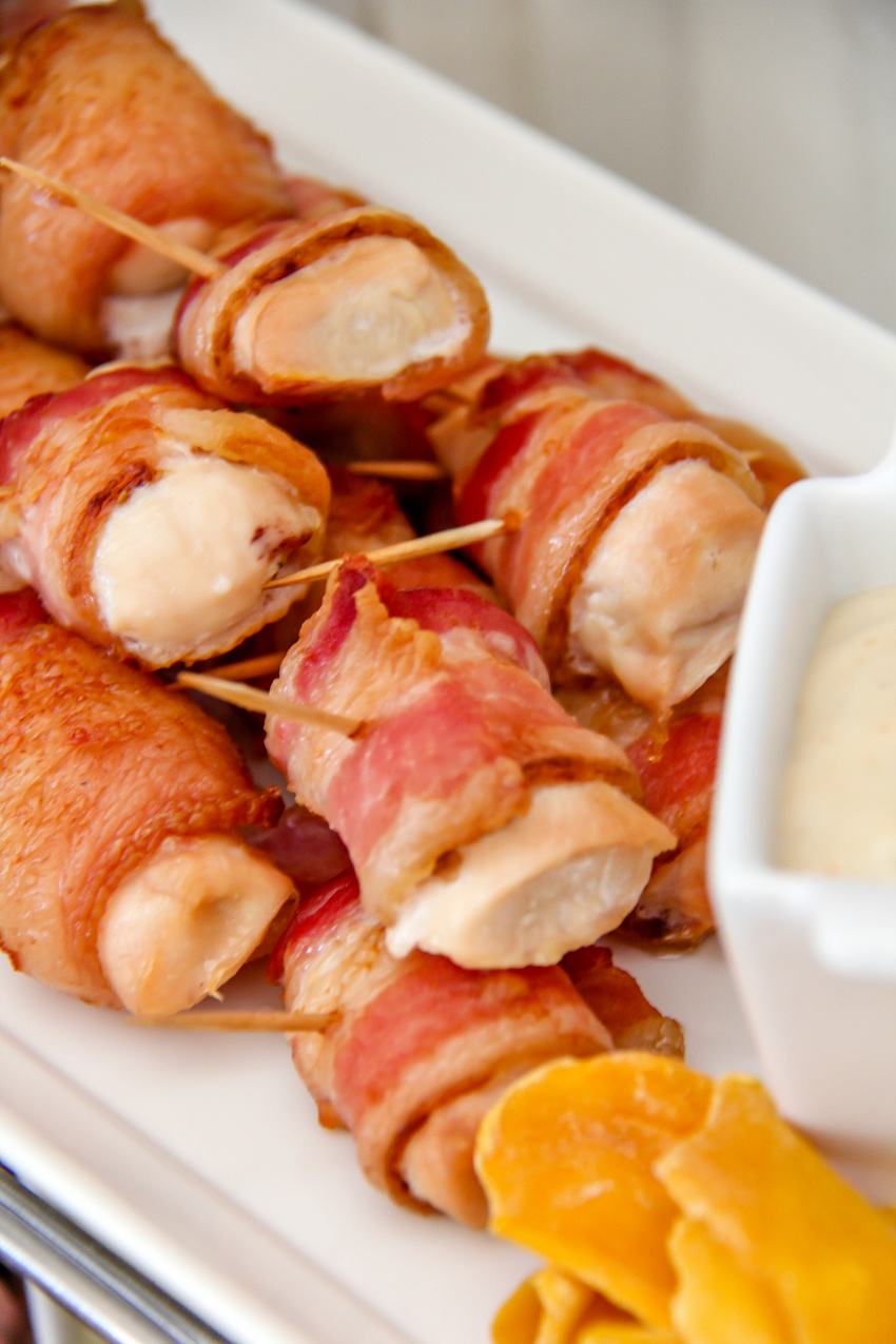 chicken pieces wrapped in bacon on a white tray