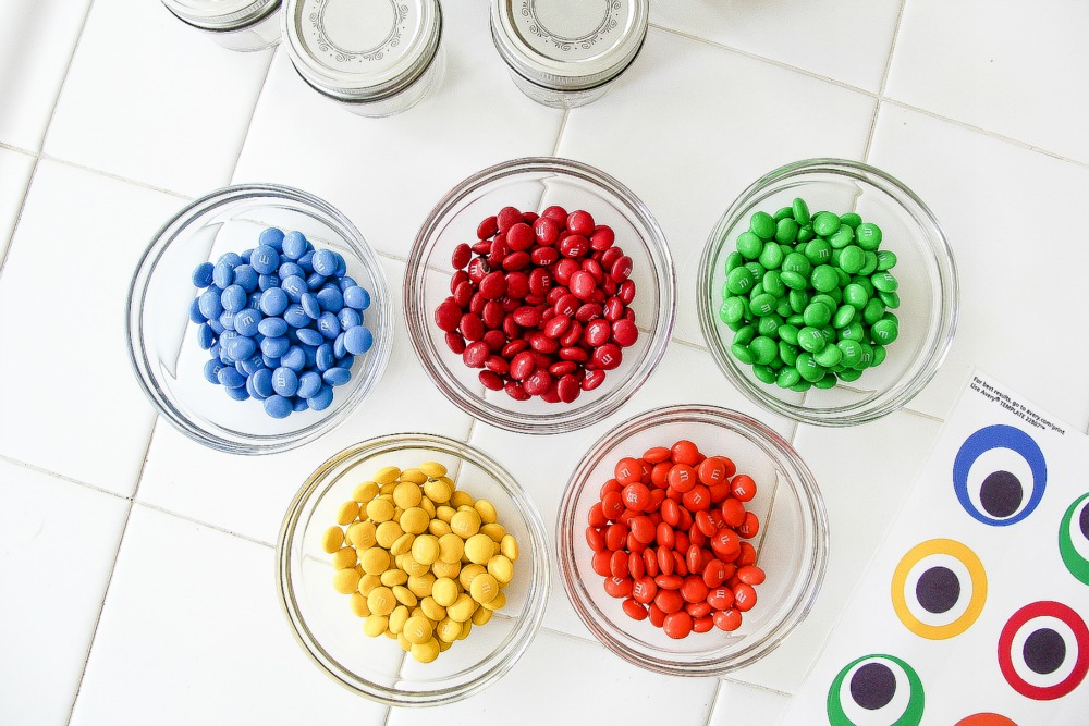 colorful M&M's candy in glass jats with monster eye labels