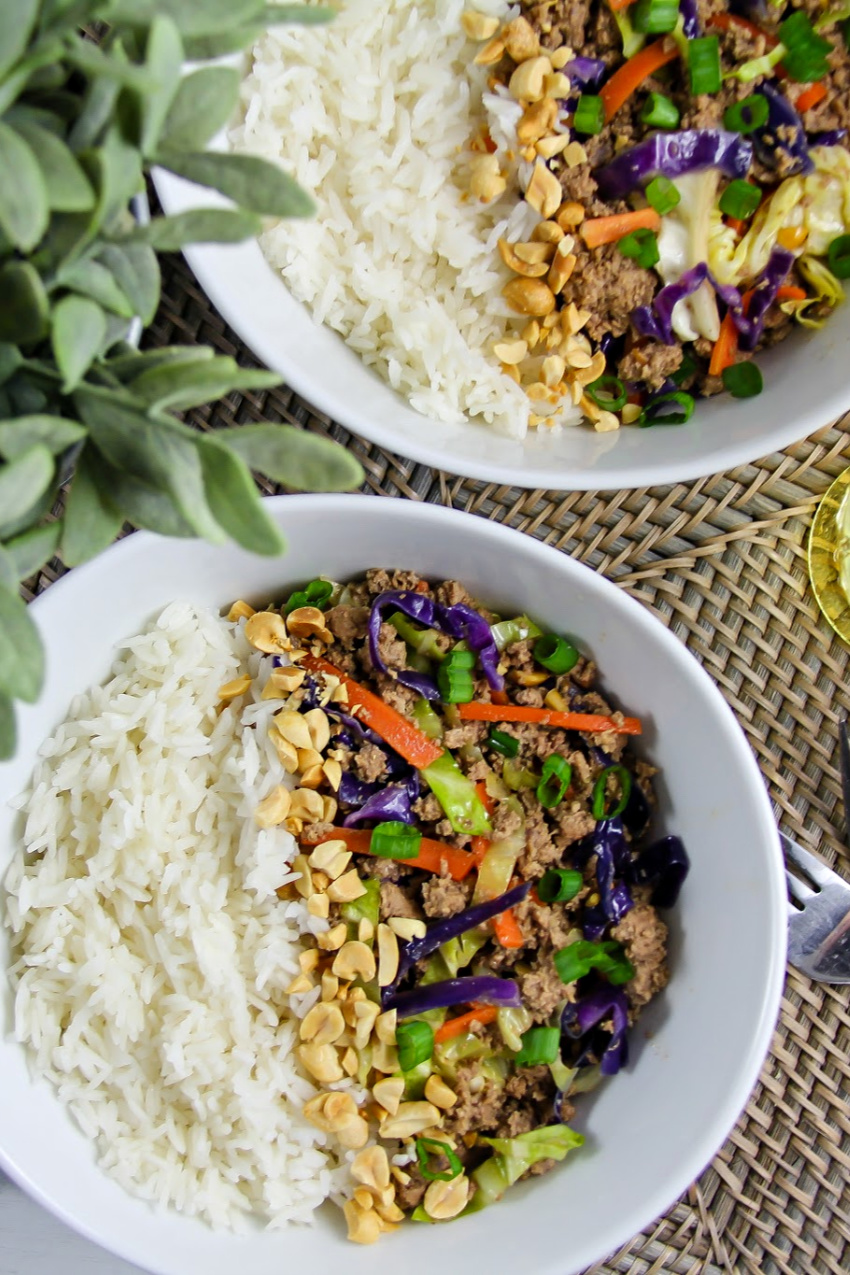 white bowls with rice on one side and ground turkey with cabbage, carrots, and green onions on the other and peanuts down the center