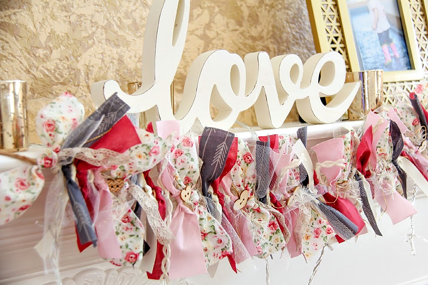pink, grey, and white fabric, ribbon, and lace garland for Valentine's Day hanging on a mantel under a love sign