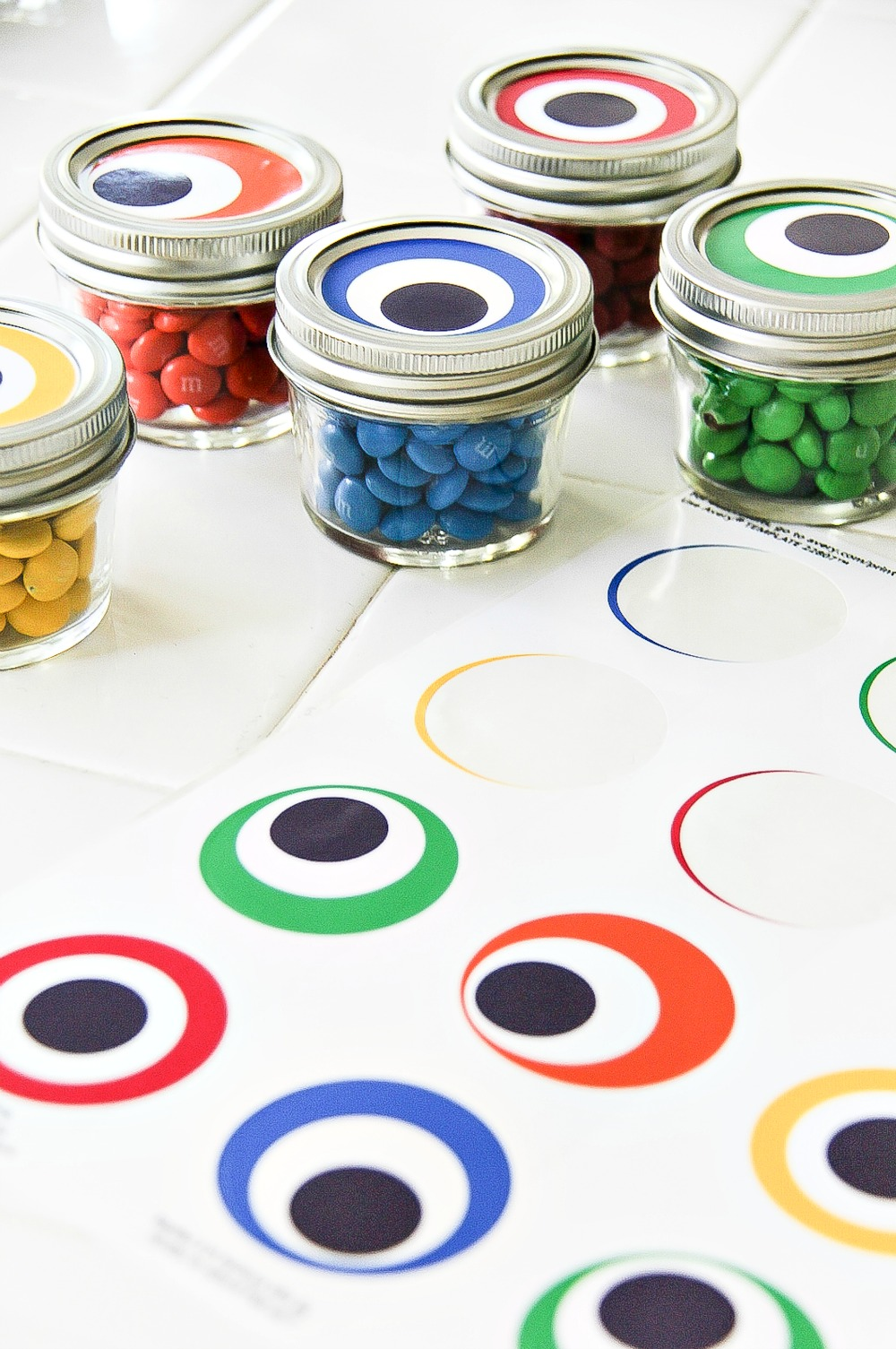 small canning jars filled with colorful candy with monster eye round labels to go on top