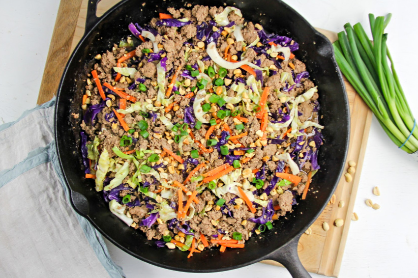 a cast iron skillet on a cutting board with a ground turkey stir fry with cabbage