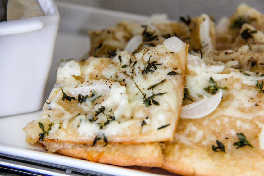 white pizza with fresh herbs cut into squares
