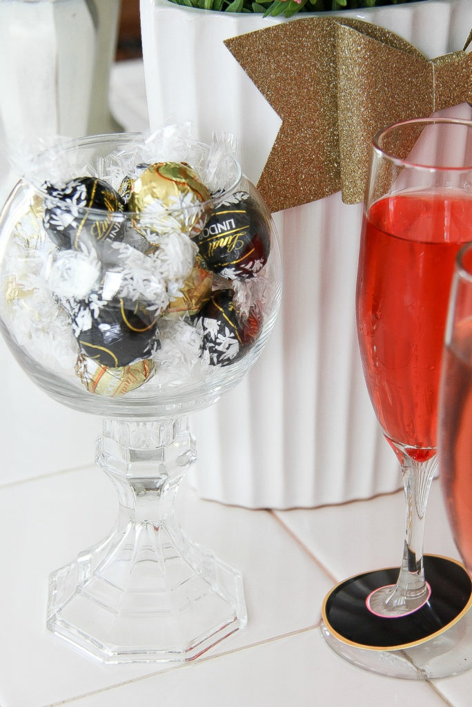 black and gold wrapped lindt balls in a glass jar