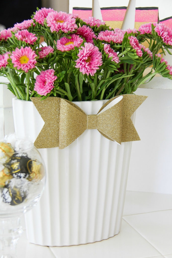 a gold glitter bow on a white vase filled with pink flowers