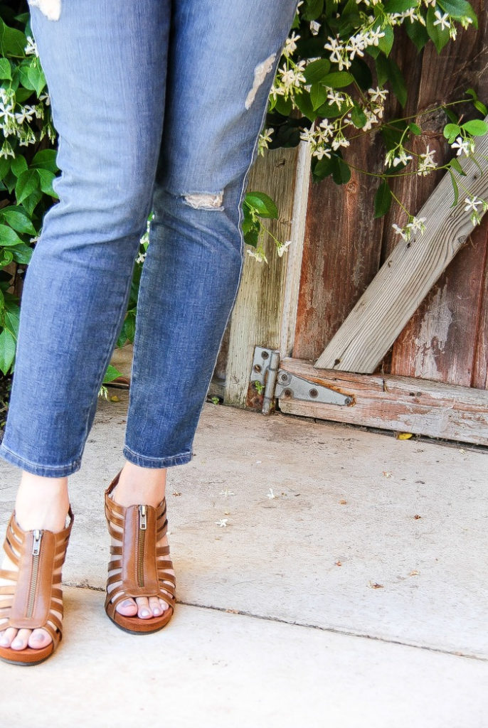lady wearing torn denim jeans with brown sandals