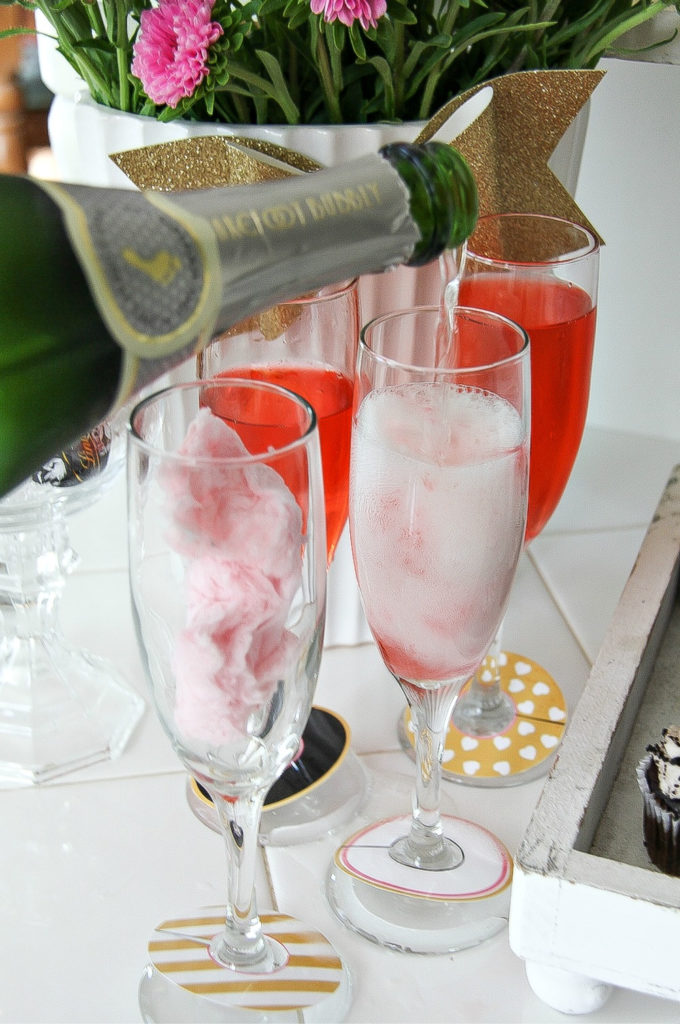barefoot bubbly being poured into a champagne glass with cotton candy in it