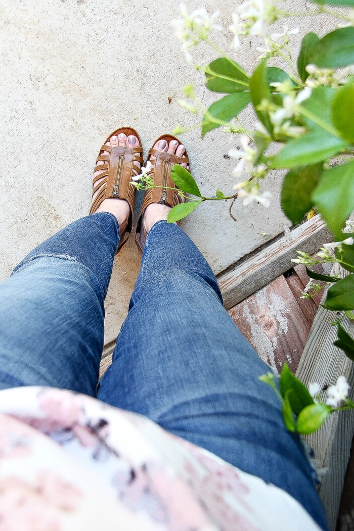 looking down denim jeans to brown sandals