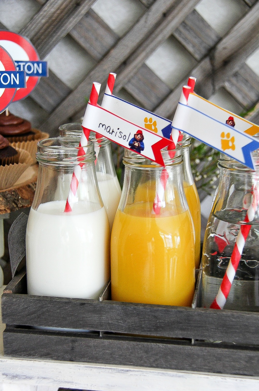 milk and orange juice in small milk bottles with flag straws with kids names on them