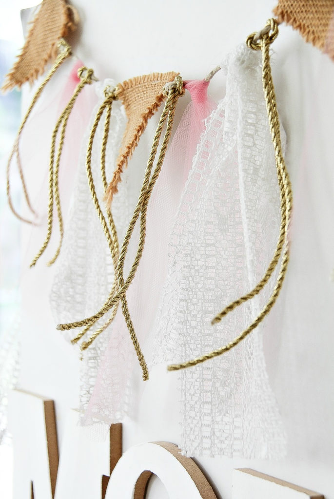 a fabric, rope, and burlap garland in pink gold and white