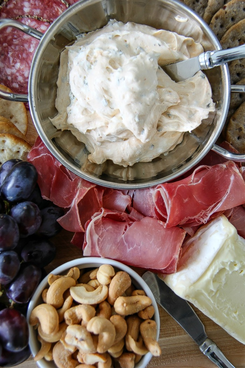 cream cheese spread in a silver bowl surrounded by meat and fruit