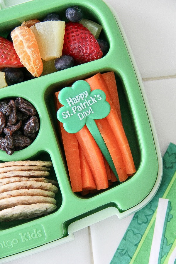 a rainbow of fruit with carrot sticks and a st patricks day pick in a lunch box
