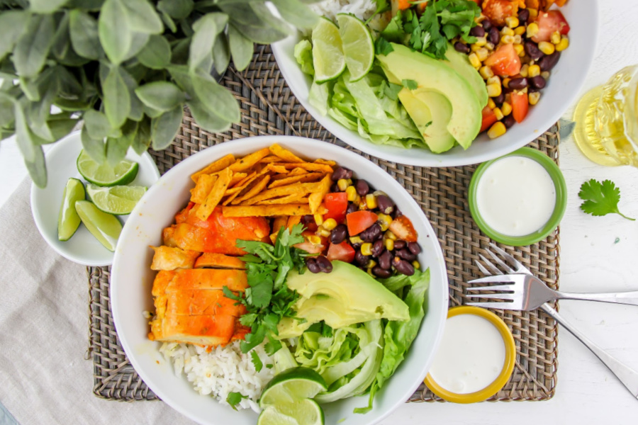 white bowls filled with chicken, rice, salsa, avocado and other taco ingredients