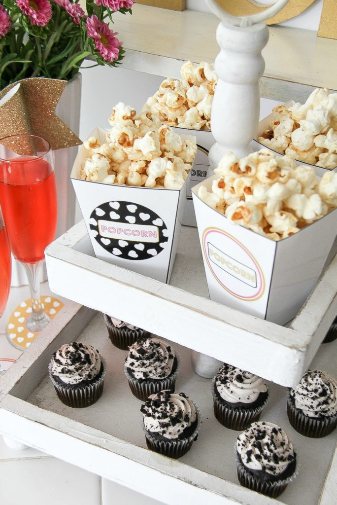a white tiered wood food stand containing popcorn and cupcakes