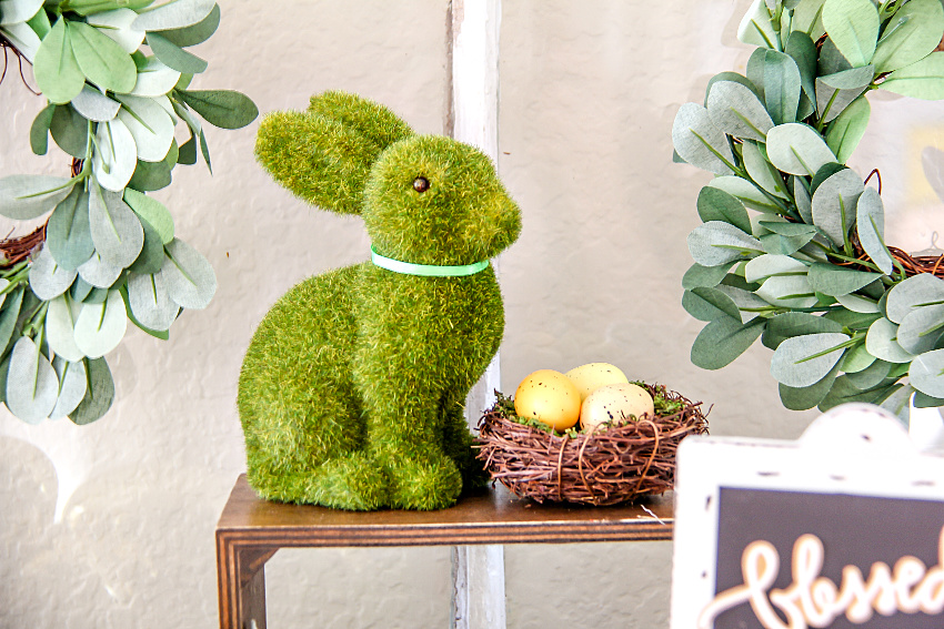 moss green bunny on a wood stand with a nest of eggs