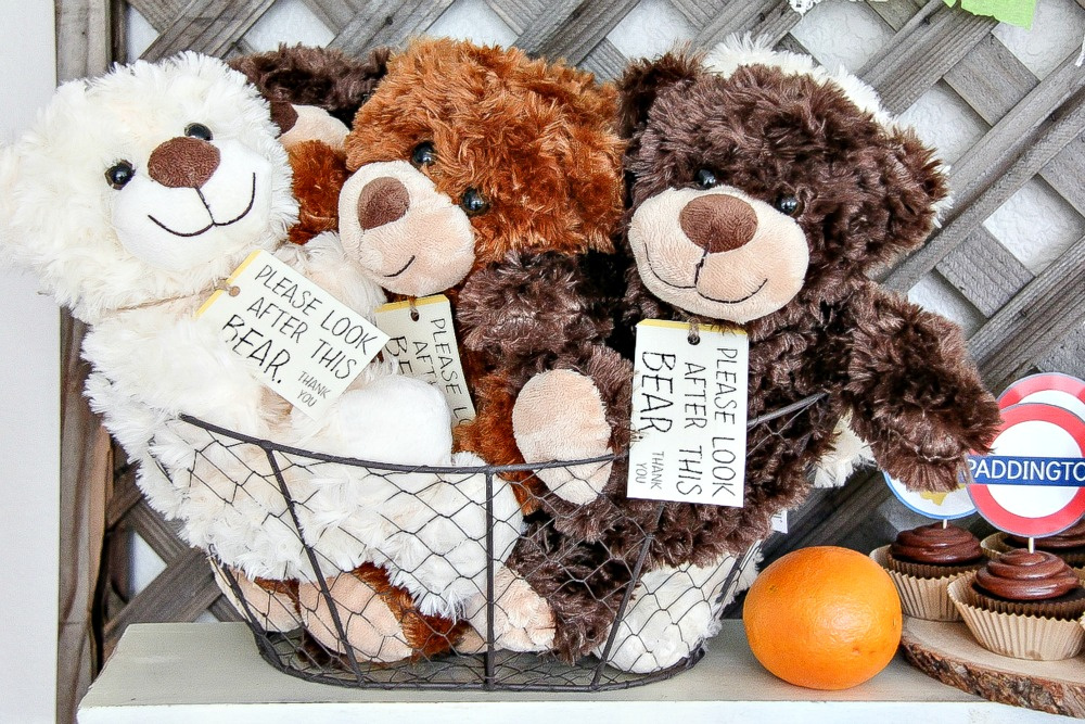 small teddy bears in a basket with a sign around their neck from paddington