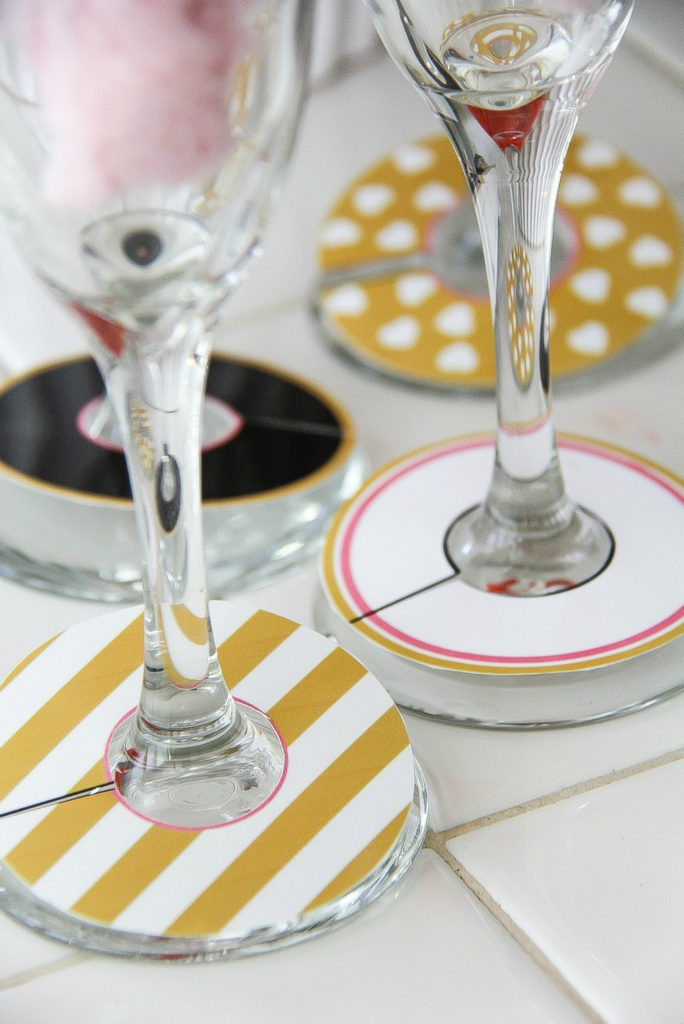 paper glass markers in black, gold, pink, and white wrapped around champagne glasses