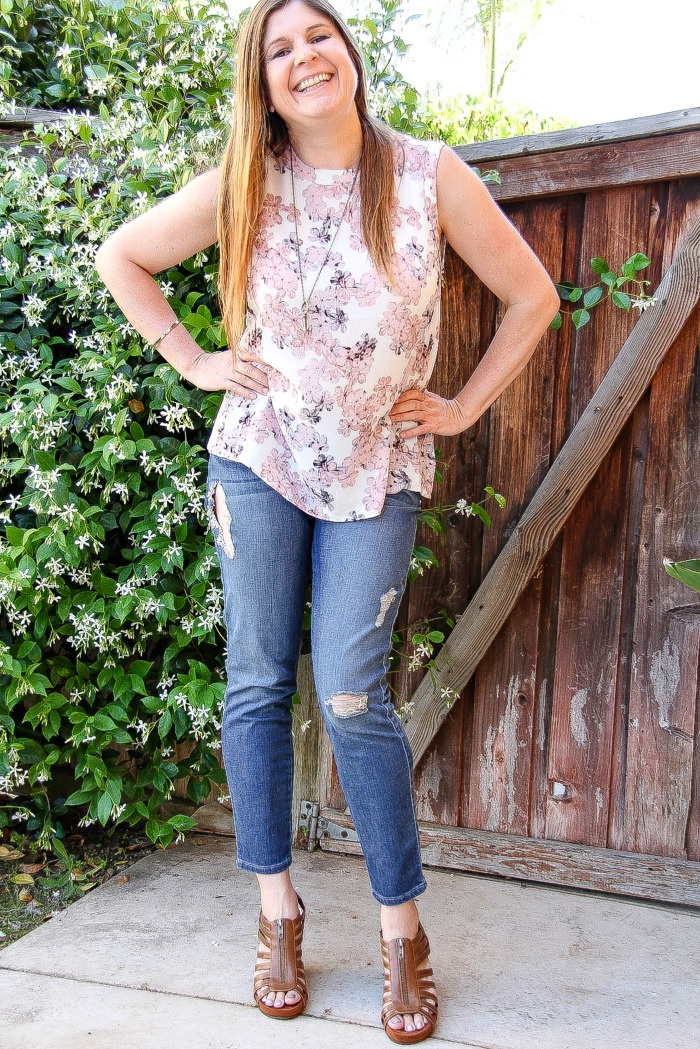 lady wearing pastel floral short sleeved shirt with torn denim jeans and brown sandals