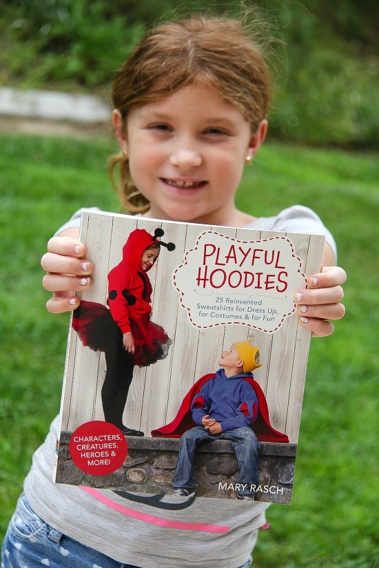 girl holding a Playful Hoodies book by Mary Rasch