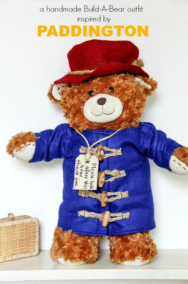 a build a bear wearing a blue duffle coat and red hat just like paddington