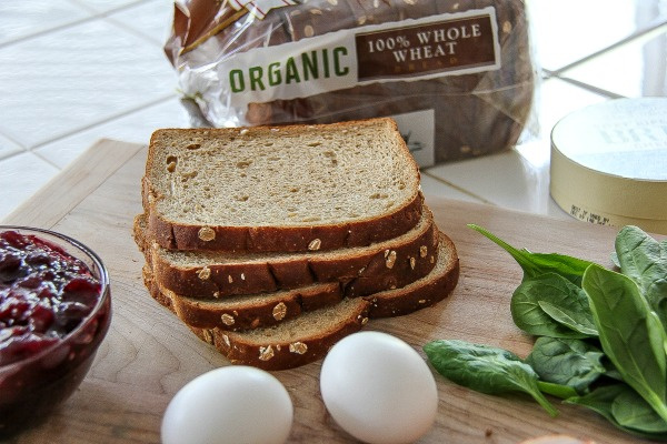 slices of whole wheat bread with eggs, cranberry sauce, and spinach